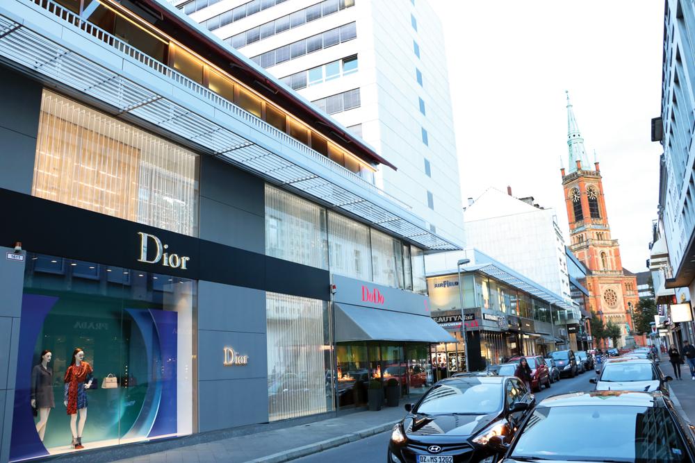 Una tienda de Dior contrasta con el campanario de una iglesia en la zona de tiendas Mertensgasse