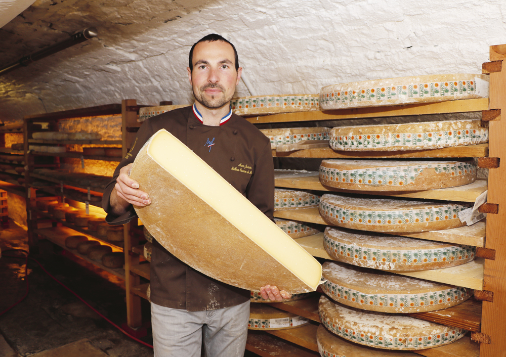 Marc Janin, sexta generación de maestros queseros del pueblo de Champagnole muestra una rueda de Comté recién cortada a la mitad, en la bodega, bajo su tienda de quesos familiar.  El Comté fue el primer queso en Francia en obtener la prestigiosa marca Denominación de Origen Controlado (AOC), en 1958.