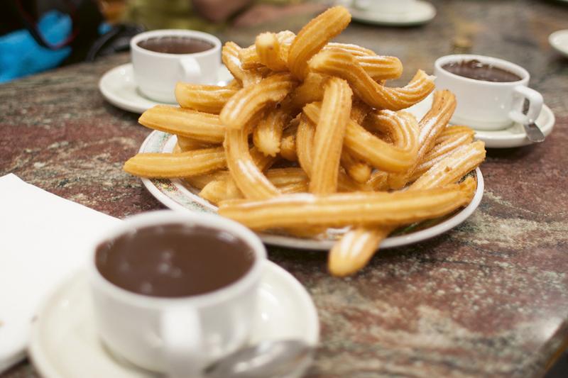 """La Buñolería-churrería de San Ginés abrió en 1894 en el pasaje del mismo nombre. Su fama empezó cuando la gente a la salida del teatro comenzó a acostumbrarse a tomar un chocolate con churros. Este establecimiento es mencionada en la obra """"Luces de Bohemia"""", de Valle Inclán."""