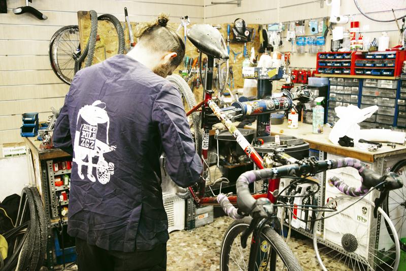 Trabajador en la tienda de reparación de bicicletas FixiDixi.