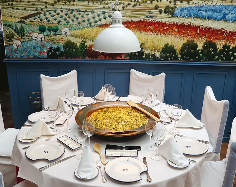 Arroz seco de la huerta servido al centro y en Patella en una de las mesas redondas de Casa Benigna.